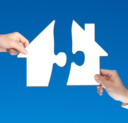 two-hands-holding-jigsaw-pieces-to-finish-house-shape-puzzle